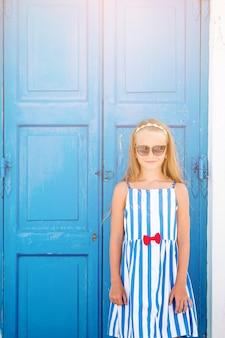 Adorable petite fille à l'ancienne rue du village traditionnel grec typique