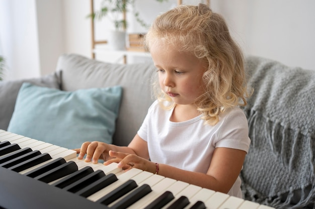 Adorable petite fille apprenant à jouer du piano à la maison