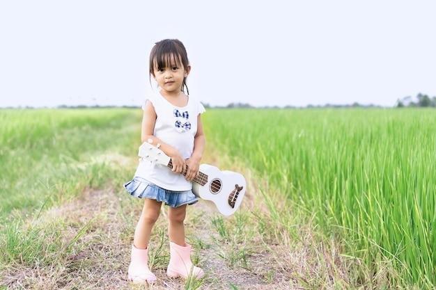 Adorable petite fille asiatique de 3 ans est debout et tenant le ukulélé blanc