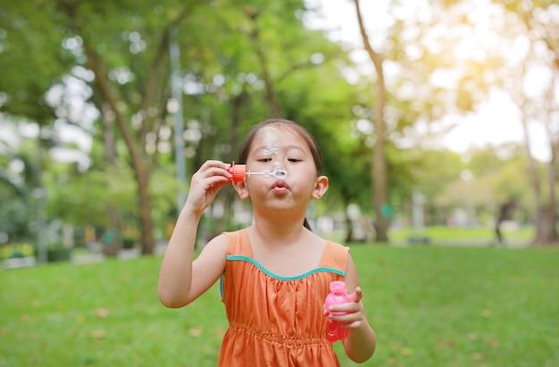 Adorable petite fille asiatique fille soufflant des bulles de savon dans un jardin verdoyant.