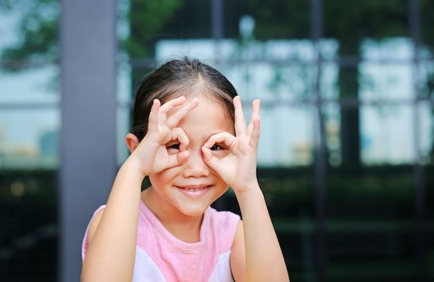 Adorable petite fille asiatique à la recherche à travers des jumelles imaginaires.