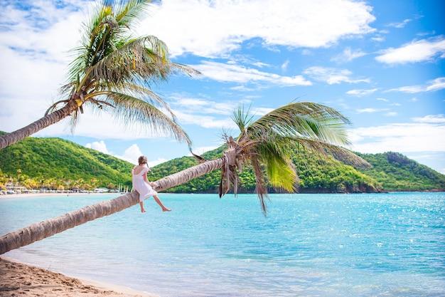 Adorable petite fille assise sur un palmier pendant les vacances d'été sur la plage blanche