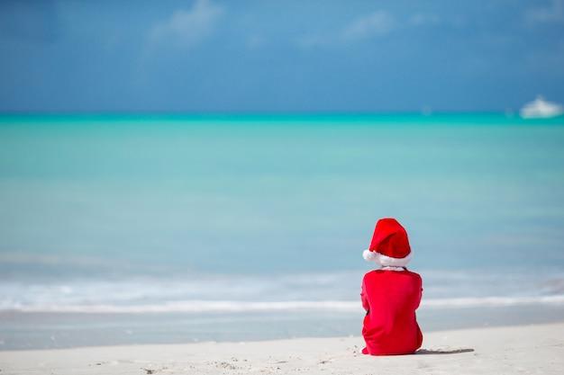 Adorable petite fille au bonnet de noel sur la plage tropicale