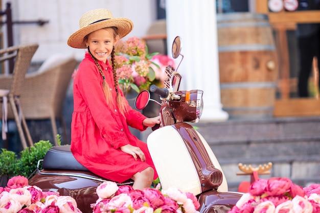 Adorable petite fille au chapeau sur le cyclomoteur à l'extérieur