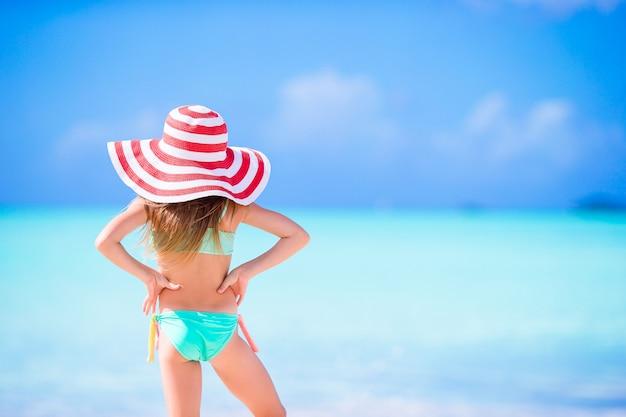 Adorable petite fille au grand chapeau marchant le long de la plage de sable blanc des caraïbes