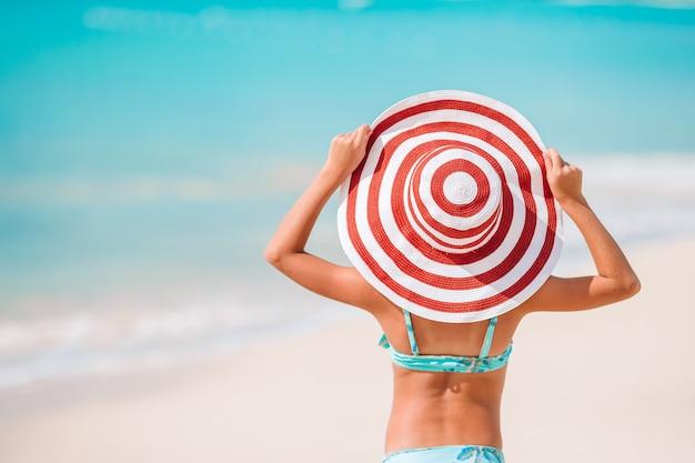 Adorable petite fille au grand chapeau rouge sur la plage