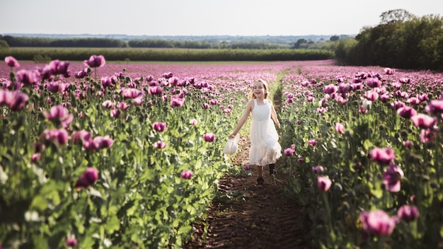 Adorable petite fille aux cheveux longs en robe blanche solitaire marchant dans le champ de lilas poppy flowers
