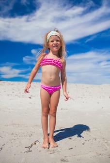 Adorable petite fille en beau maillot de bain s'amuser à la plage tropicale