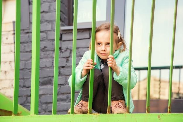 Adorable petite fille blonde caucasienne assise avec un visage ennuyé sur l'escalier en fer en regardant la caméra.