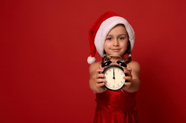 Adorable petite fille en bonnet de noel et costume montre minuit sur l'horloge du réveil, sourit en regardant la caméra et pose sur fond rouge avec espace de copie. bonne année, joyeux noël