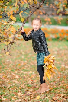 Adorable petite fille avec un bouquet de feuilles jaunes en automne en scooter