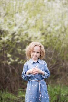 Adorable petite fille caucasienne de 5 ans dans un parc debout sous un cerisier en fleurs