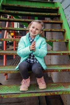 Adorable petite fille caucasienne assise sur l'escalier en fer avec intérêt en regardant les passants