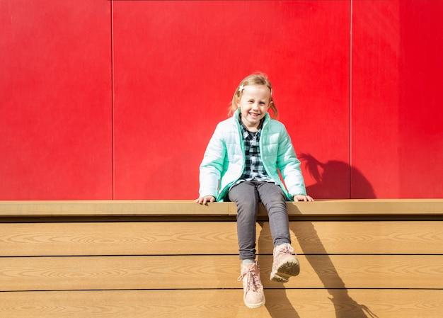 Adorable petite fille caucasienne assise sur une terrasse en bois à côté d'un mur rouge en regardant la caméra