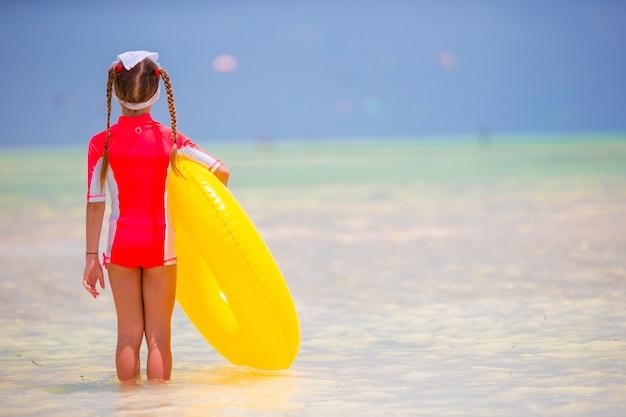Adorable petite fille avec cercle de caoutchouc gonflable pendant les vacances à la plage. kid s'amuser en vacances actives d'été