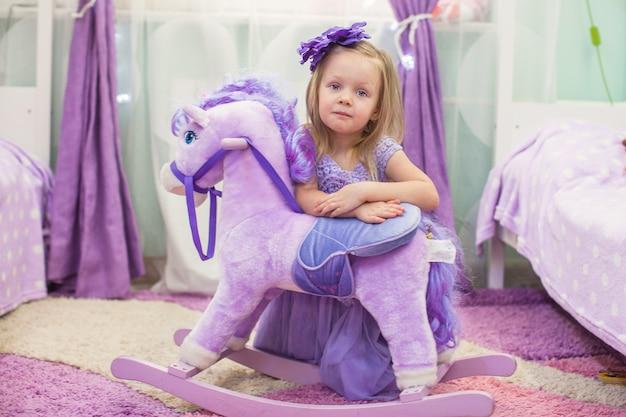Adorable petite fille avec un cheval en peluche à la maison