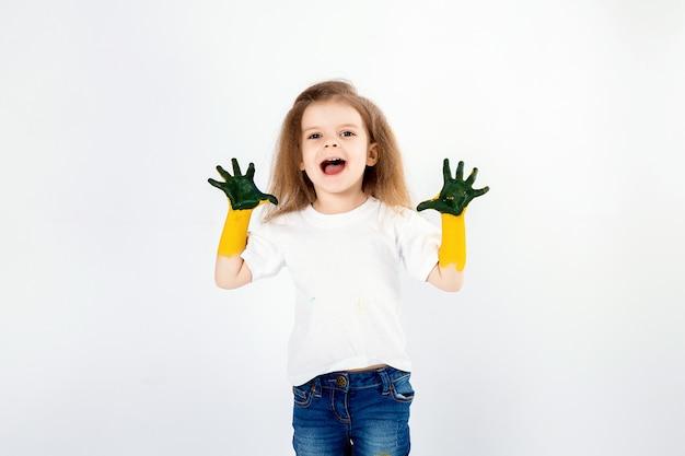 Adorable petite fille, coiffure moderne, chemise blanche, jeans, pose, hurlement, rugissement, sourire. elle a peint de la peinture sur ses mains. isolé. blanc.