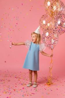 Adorable petite fille en costume avec des ballons