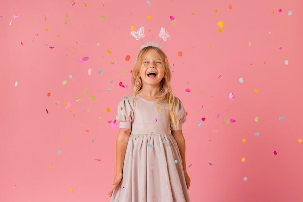 Adorable petite fille en costume avec des confettis