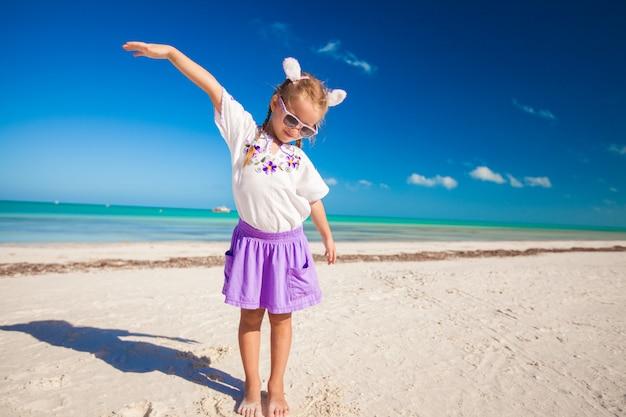 Adorable petite fille en costume de pâques sur la plage exotique