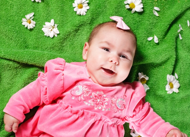 Adorable petite fille couchée sur le pré et sourire