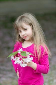Adorable petite fille dans un jardin de cerisiers en fleurs par une belle journée de printemps.