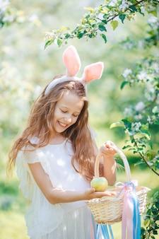 Adorable petite fille dans un jardin de pommes en fleurs sur une belle journée de printemps