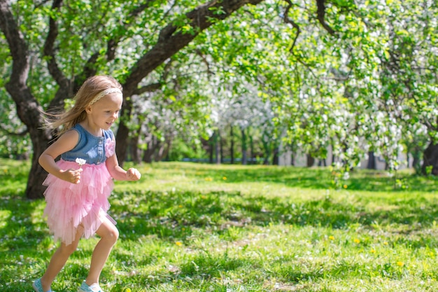 Adorable petite fille dans un jardin de pommiers fleuri