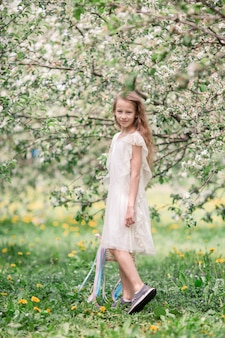 Adorable petite fille dans un jardin de pommiers en fleurs sur une belle journée de printemps