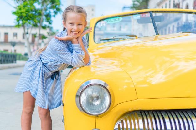 Adorable petite fille dans un quartier populaire de la vieille havane, à cuba. portrait d'enfant, voiture américaine classique vintage
