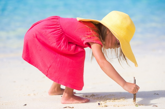 Adorable petite fille dessinant sur le sable blanc à la plage