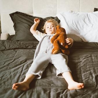 Adorable petite fille détendue jouant avec un ours en peluche sur un grand lit à la maison