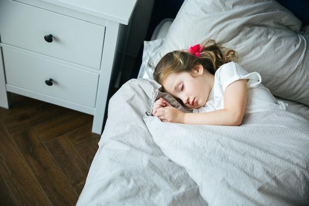 Adorable petite fille dormant dans son lit en pyjama sous la couverture chez elle, calme et paisible