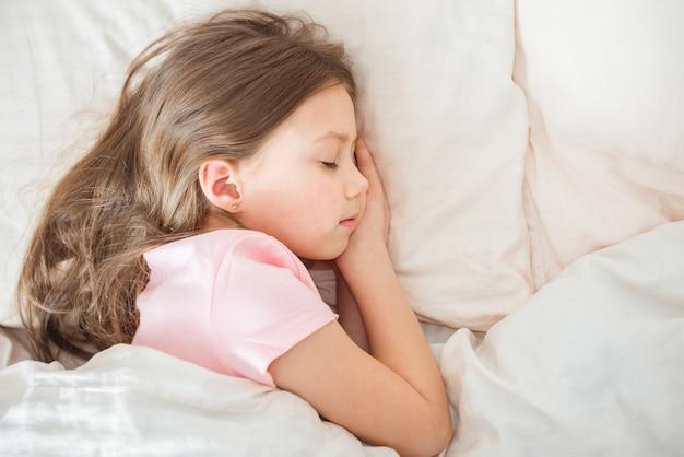 Adorable petite fille dort dans le lit