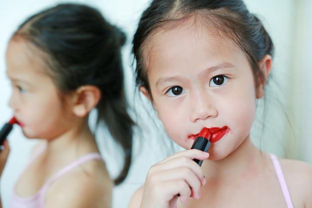 Adorable petite fille drôle, appliquer le rouge à lèvres sur sa bouche