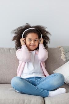 Adorable petite fille écoutant de la musique