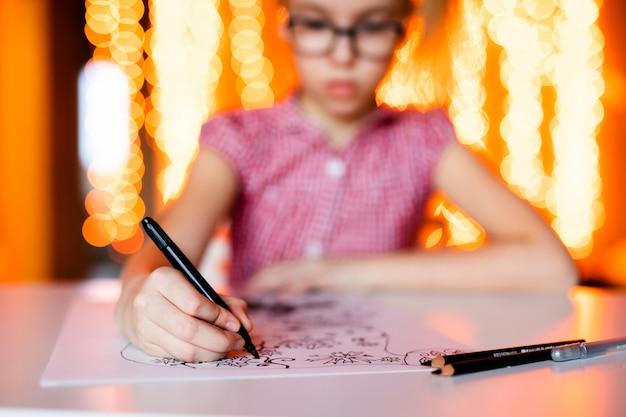 Adorable petite fille écrit une lettre au père noël assis sur la table