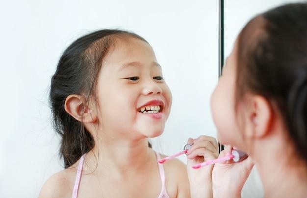 Adorable petite fille enfant asiatique essayant de brillant à lèvres devant un miroir.