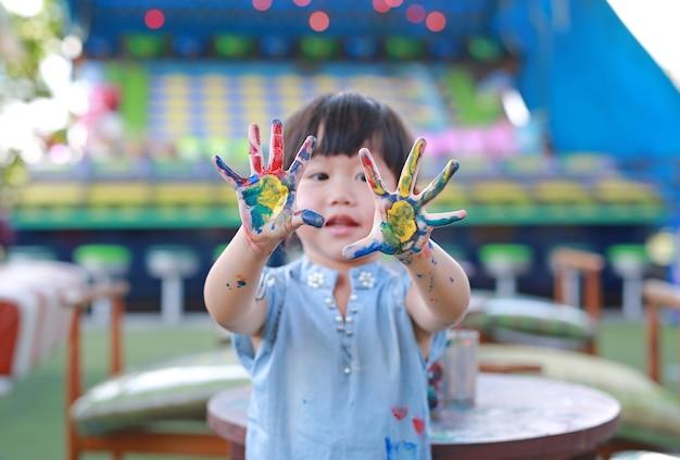 Adorable petite fille enfant asiatique montrant des mains peintes.