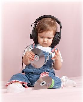 Adorable petite fille est assise et écoute de la musique en rose