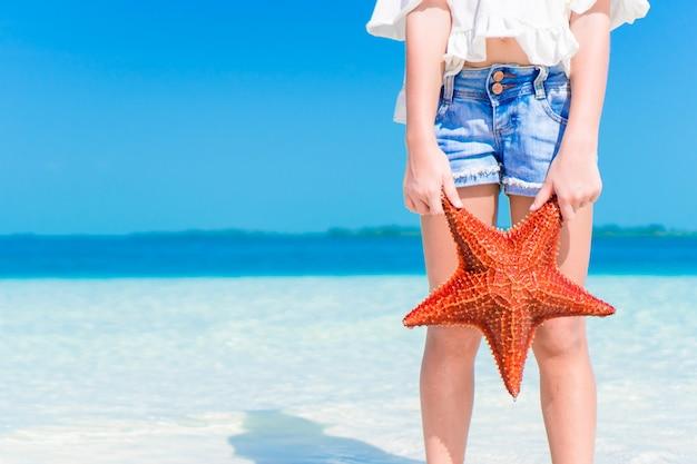 Adorable petite fille avec une étoile de mer sur une plage vide blanche