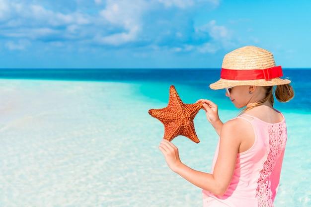 Adorable petite fille avec des étoiles de mer sur une plage vide blanche