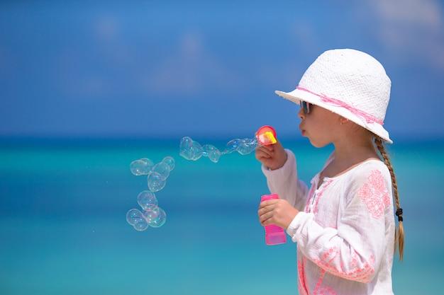 Adorable petite fille faisant des bulles de savon pendant les vacances d'été