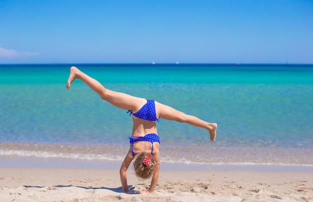 Adorable petite fille faisant la roue sur la plage de sable blanc tropicale