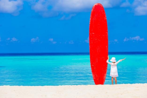 Adorable petite fille avec une grosse planche de surf pendant des vacances tropicales