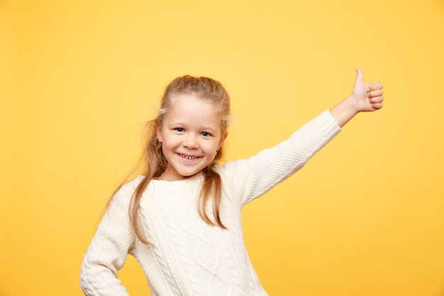 Adorable petite fille heureuse debout isolé sur jaune