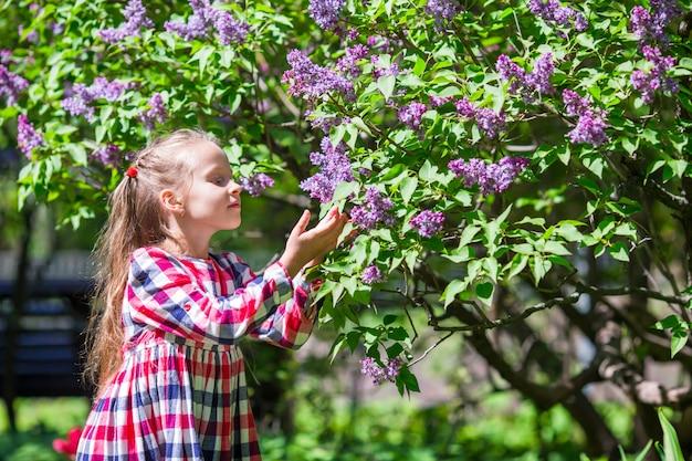 Adorable petite fille heureuse avec panier dans un jardin de fleurs lilas