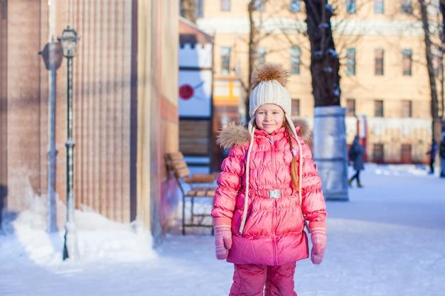 Adorable petite fille heureuse en train de patiner à la patinoire