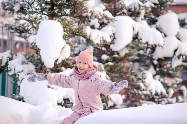 Adorable petite fille heureuse, traîneau à chiens en journée d'hiver enneigée.