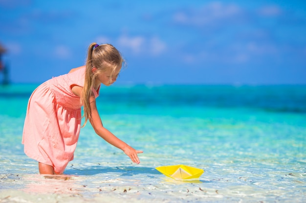 Adorable petite fille jouant avec un bateau origami en mer turquoise